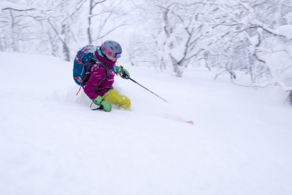 woman backcountry skiing in deep powder snow in japan