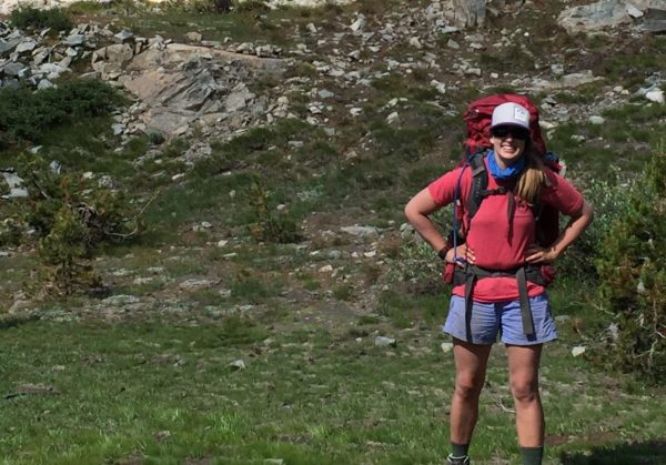 Author in her backpacking outfit, shorts, tshirt, boots, socks, trucker hat, sunglasses, 70 liter backpack
