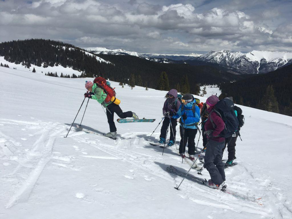 backcountry ski guide shows climbing skins and kick turn demo