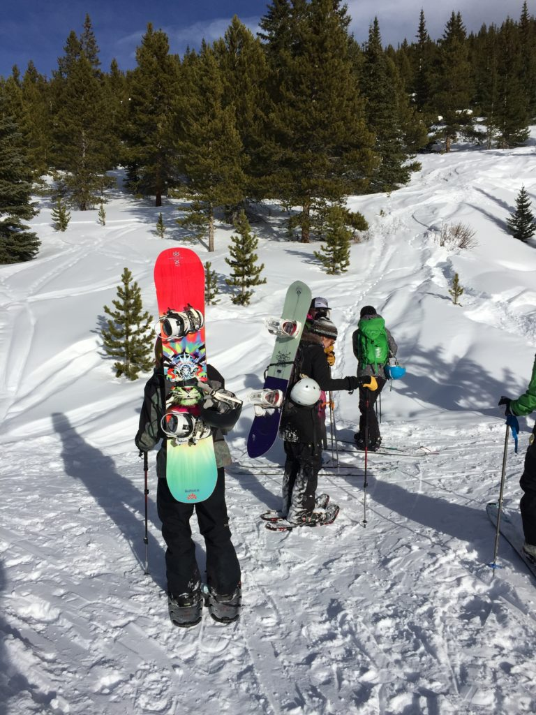 hiking in snowshoes with a snowboard on the backpack